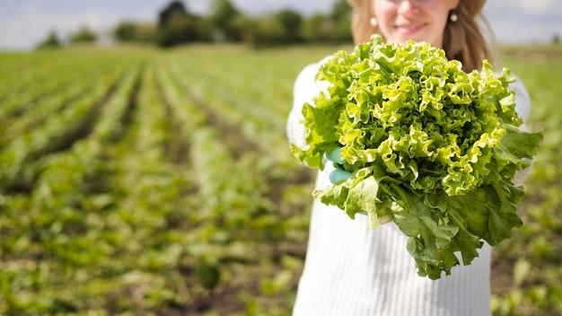 Mujer sosteniendo un vegetal verde con espacio de copia