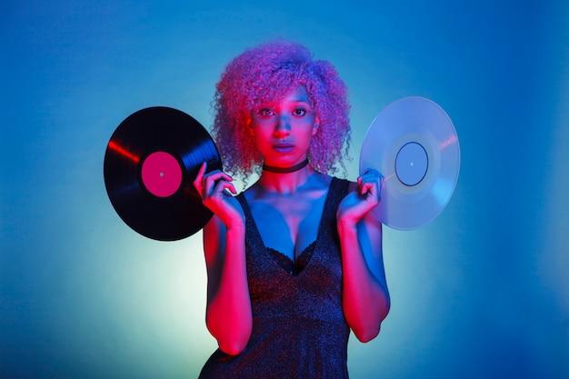 Mujer sosteniendo viejos vinilos de música en coloridas luces de neón