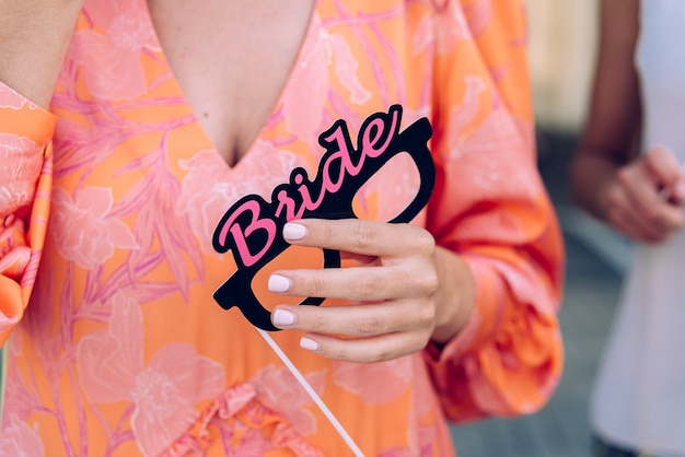 Una mujer sostiene un accesorio con la palabra novia durante una fiesta de disfraces