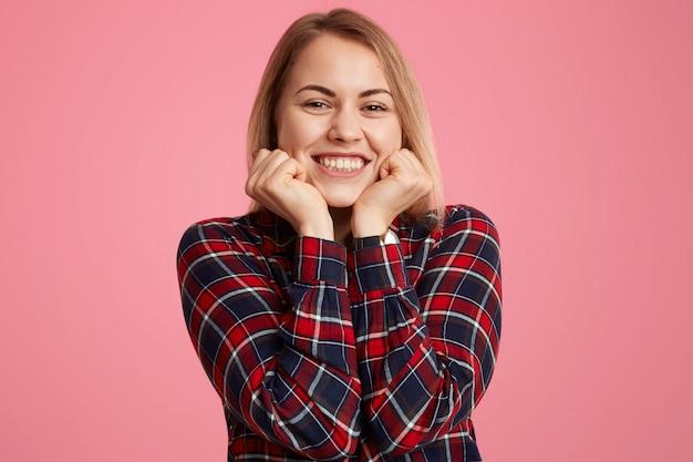 La mujer sostiene la barbilla, sonríe ampliamente, muestra dientes blancos y perfectos, está de buen humor, vestida casualmente