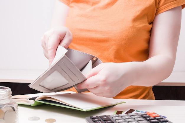 Mujer sostiene una billetera vacía en la oficina
