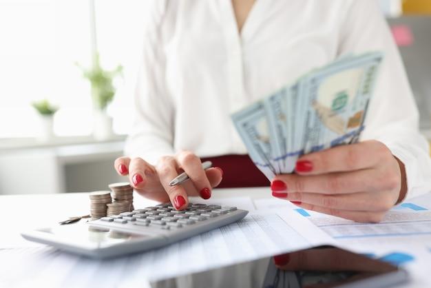 La mujer sostiene los billetes americanos en sus manos y trabaja en la calculadora
