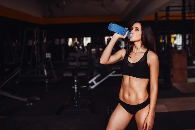 La mujer sostiene la botella azul con el agua que se coloca en el gimnasio