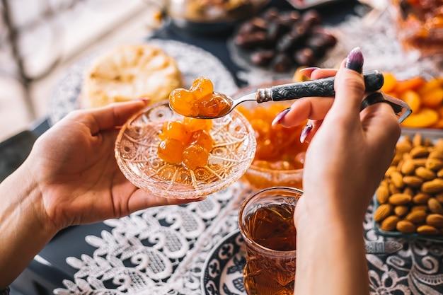 Mujer sostiene una cacerola de cristal con mermelada de cereza y una cucharadita