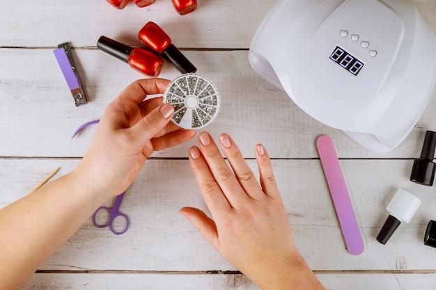 Mujer sostiene caja con pedrería de manicura