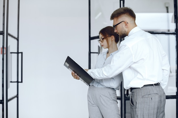La mujer sostiene una carpeta. socios comerciales en una reunión de negocios. personas con gafas