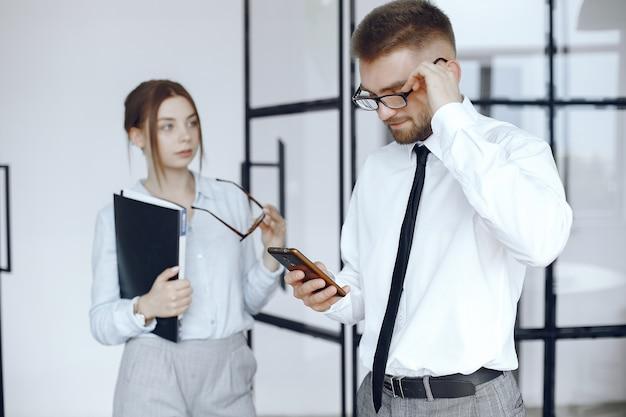 La mujer sostiene una carpeta. socios de negocios en una reunión de negocios. hombre usa el teléfono. personas con gafas