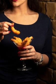 Mujer sostiene una copa de cóctel de camarones fritos en salsa de chile dulce