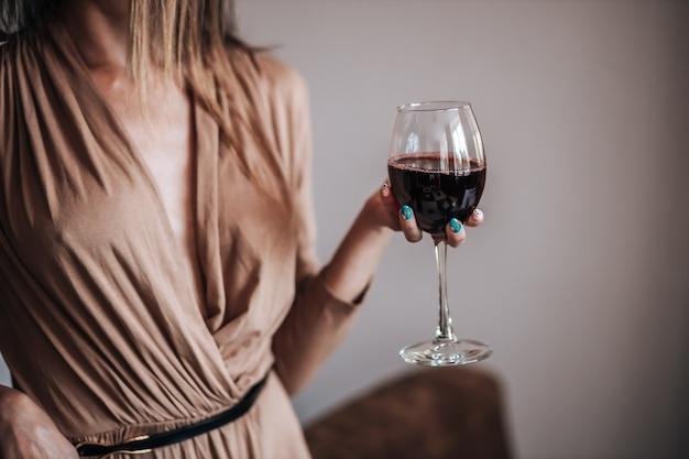 Una mujer sostiene una copa de vino tinto en un restaurante