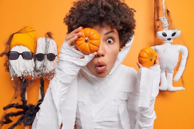 Mujer sostiene dos pequeñas calabazas mira sorprendida viste traje de fantasma blanco rodeado de juguetes de halloween aislado en naranja