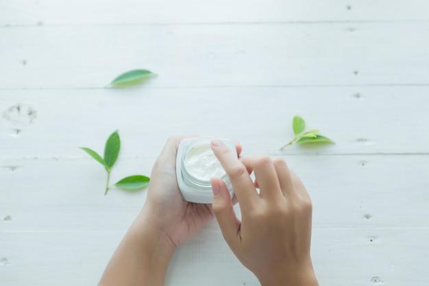 Mujer sostiene un frasco con una crema cosmética en sus manos