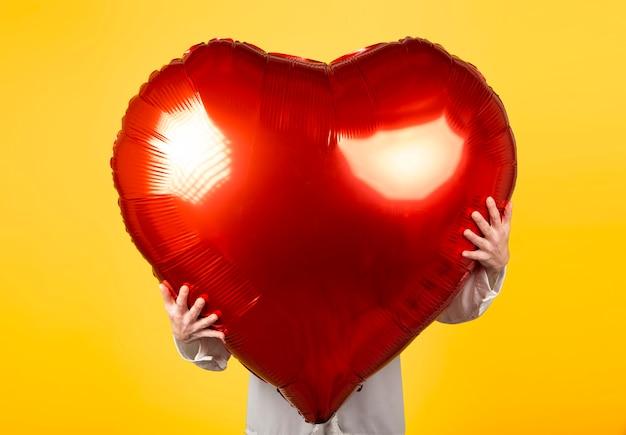 La mujer sostiene el globo rojo de forma de corazón muy grande. concepto de día de san valentín