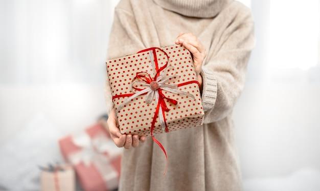 Una mujer sostiene un hermoso regalo de navidad.