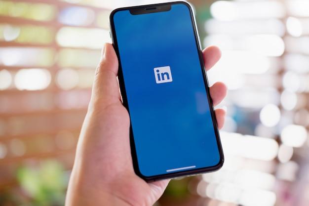 Una mujer sostiene el iphone xs con la aplicación linkedin en la pantalla. linkedin es una aplicación para compartir fotos para teléfonos inteligentes.