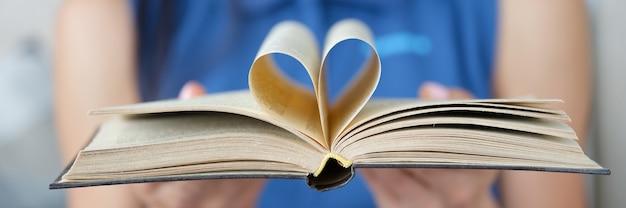 La mujer sostiene el libro con una página en forma de corazón doblado en el centro