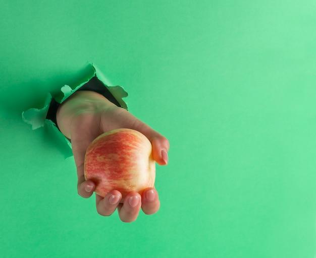 Una mujer sostiene una manzana en su mano, insertada a través de un agujero en papel verde rasgado