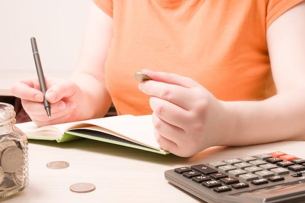 Una mujer sostiene una moneda de 10 rublos y escribe algo en un cuaderno.