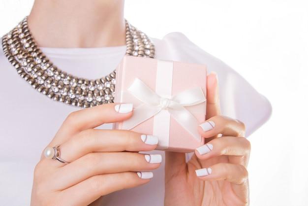La mujer sostiene una pequeña caja de regalo aislada en blanco