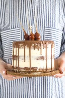 Una mujer sostiene un pequeño pastel redondo hermoso lleno de chocolate.
