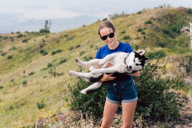 La mujer sostiene un perro en sus brazos. husky en la naturaleza.