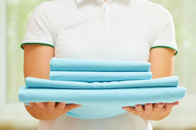 Una mujer sostiene una pila de ropa de cama limpia y azul.