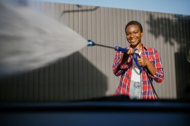 Mujer sostiene pistola de agua a alta presión, lavado de autos
