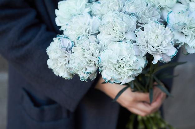 La mujer sostiene un ramo de claveles azules