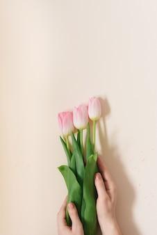 La mujer sostiene un ramo de delicados tulipanes rosados.
