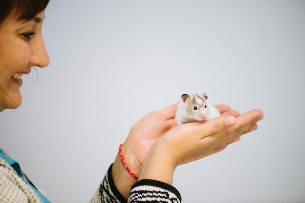 La mujer sostiene el ratoncito peludo blanco.