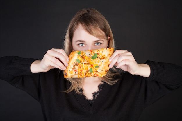 Una mujer sostiene rebanadas de pizza y las lanza como cuchillos. foto de concepto para publicidad de pizza.