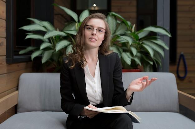 Mujer sostiene una reunión y conferencia en línea mira a la cámara
