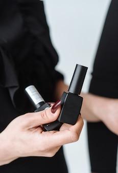 La mujer sostiene el rimel negro en su mano