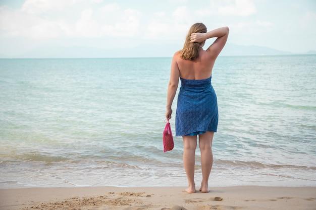 Una mujer sostiene en su mano una bolsa de malla y se encuentra en el borde del mar en una playa de arena