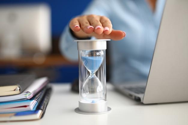 La mujer sostiene su mano sobre el reloj de arena en el lugar de trabajo en la oficina de cerca