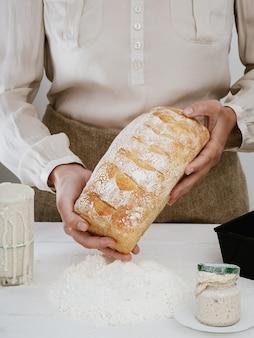 Mujer sostiene en sus manos pan de masa fermentada recién horneado