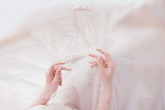 Mujer sostiene en sus manos tarjeta transparente con una inscripción