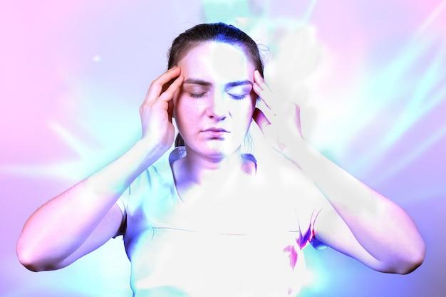 Una mujer sostiene sus manos por el templo, concentrándose durante la meditación.
