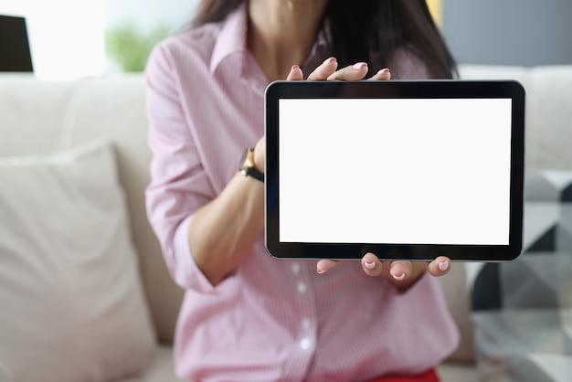 La mujer sostiene la tableta negra en su primer de las manos