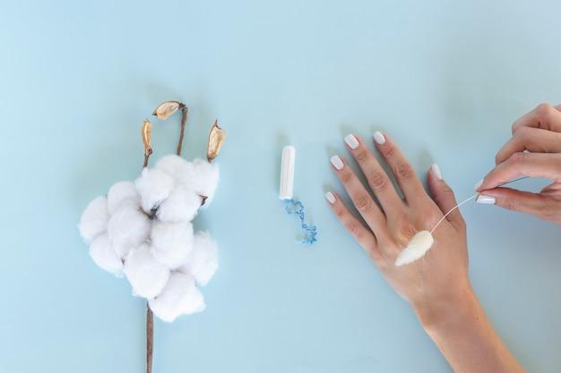 Una mujer sostiene un tampón sanitario blanco en sus manos. días de menstruación. concepto de higiene y cuidado corporal.