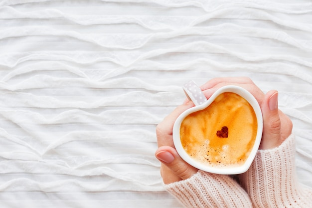 Mujer sostiene una taza de café caliente con corazón de canela