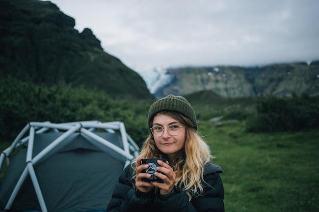 Mujer sostiene taza de camping en viaje de senderismo en islandia