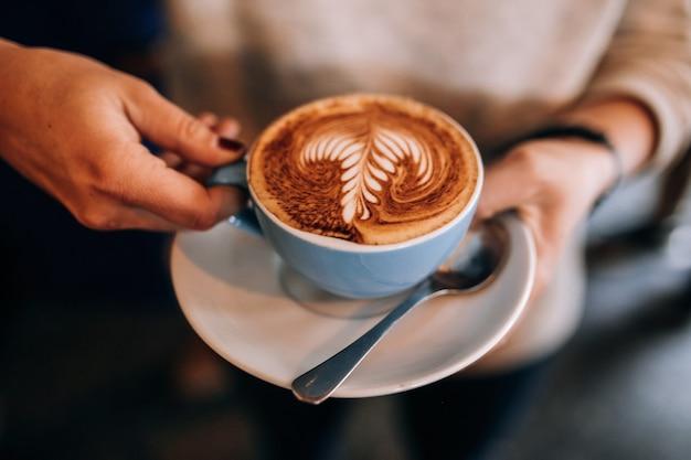 La mujer sostiene la taza en el platillo con café con leche caliente