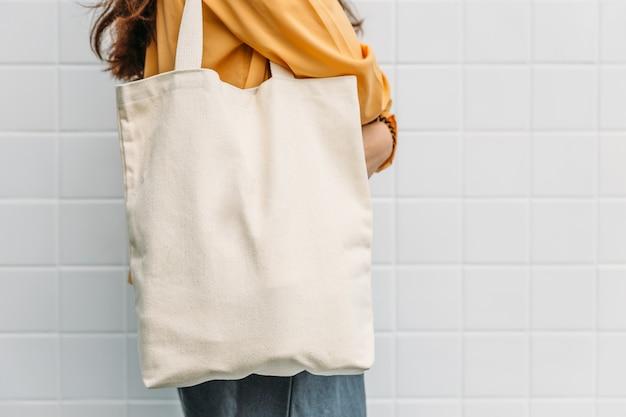 La mujer sostiene la tela de la lona de la bolsa de asas para la plantilla en blanco de la maqueta.