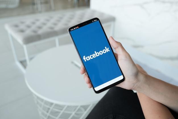 La mujer sostiene el teléfono inteligente con la aplicación de facebook en la pantalla. facebook es una aplicación para compartir fotos para teléfonos inteligentes