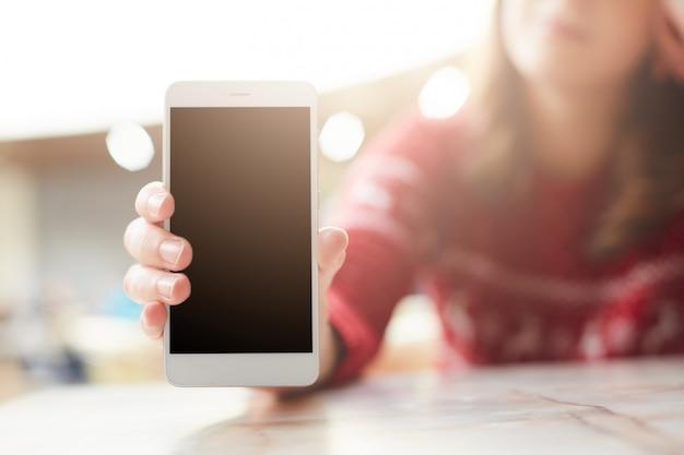 La mujer sostiene el teléfono inteligente blanco moderno