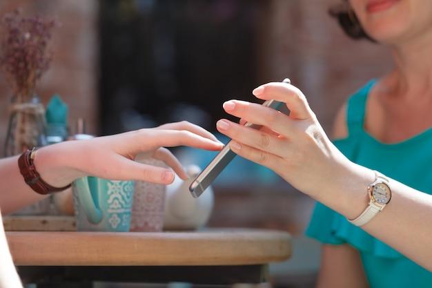 La mujer sostiene un teléfono inteligente en su mano sobre una mesa en un café, muestra a su amiga una pantalla con una foto