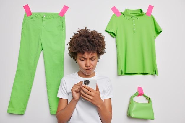 Mujer sostiene el teléfono móvil molesto para recibir un mensaje con malas noticias posa en la ropa pegada a la pared blanca crea contenido multimedia en línea