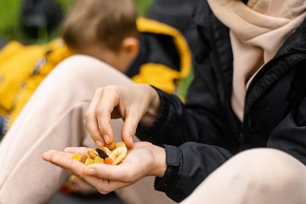 Una mujer sostiene varios frutos secos y nueces en su mano. se sienta en la hierba verde del bosque. refrigerio durante la caminata, caminata. comida vegetariana saludable.