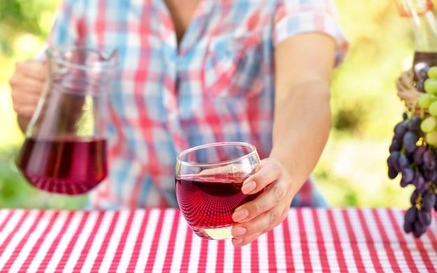 Mujer sostiene un vaso de vino o jugo de uva sobre la mesa con mantel rojo