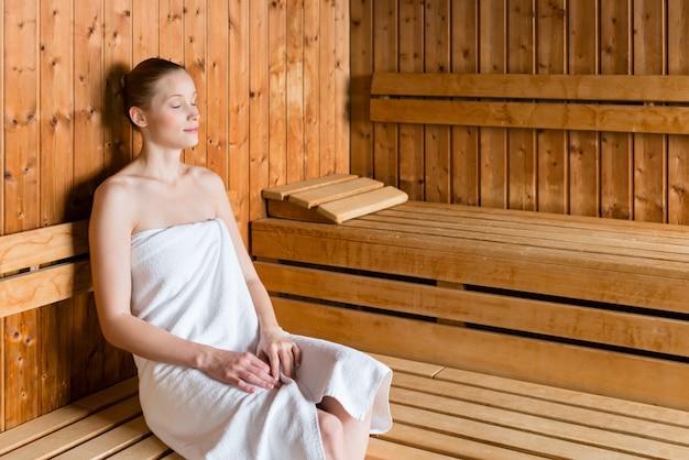 Mujer en spa de bienestar disfrutando de sauna